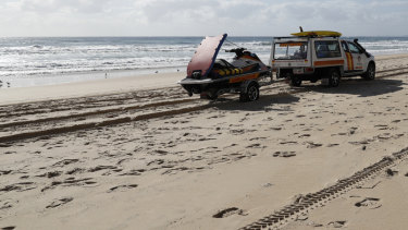 A surf lifesaving crew drives past the scene at Surfers Paradise where a baby's body was found.