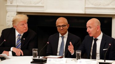 Not much love lost: Donald Trump (with Microsoft CEO Satya Nadella in the centre) listens to Amazon boss Jeff Bezos during an American Technology Council roundtable at the White House last year.