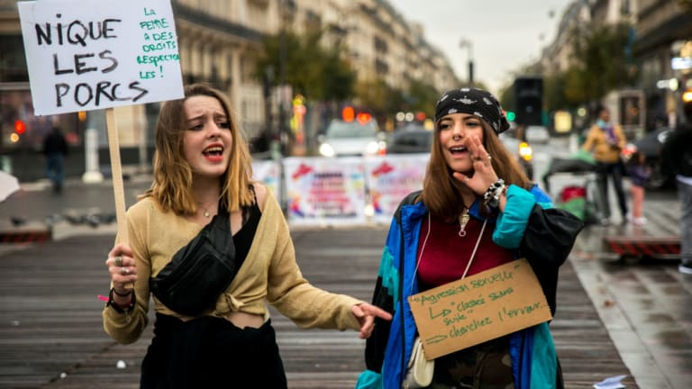 Protesters hold placards and shout slogans as they take part in a gathering against gender-based and sexual violence on the Place de la Republique square in Paris.