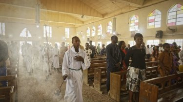 An altar boy swings the thurible of incense during a morning service at the Saint Charles Catholic Church, the site of a 2014 bomb attack blamed on Islamic extremist group Boko Haram in Kano, northern Nigeria.