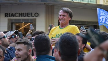 Presidential candidate Jair Bolsonaro grimaces right after being stabbed in the stomach during a campaign rally in Juiz de Fora.