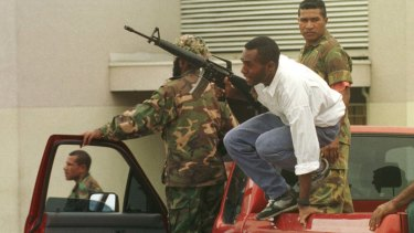 PNG defence forces attempt to disperse protesters in Port Moresby.