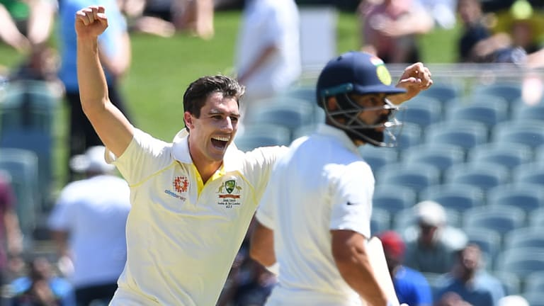 Pat Cummins celebratesVirat Kohli's wicket as the batsman stands at the crease after Usman Khawaja's catch.