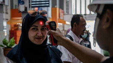 A security checks a passenger's body temperature at Tugu train station on March 12, 2020 in Yogyakarta, Indonesia.
