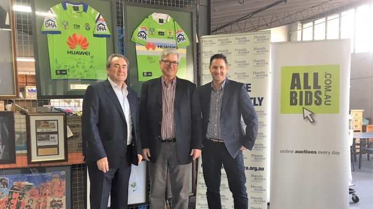 ActewAGL's Paul Walshe, Hands Across Canberra CEO Peter Gordon and Allbids Auctions CEO Rob Evans with some of the items.