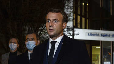 French President Emmanuel Macron, flanked by French Interior Minister Gerald Darmanin, second left, speaks in front of a high school northwest of Paris, after a history teacher was beheaded.