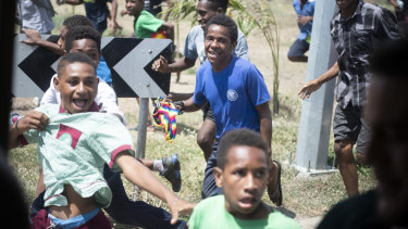 Mobs of children run alongside the Prime Minister's XIII's team bus in Port Moresby on Thursday.