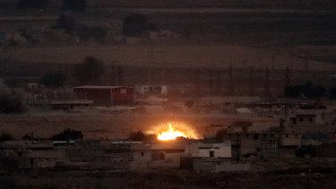 Fire is seen in the Syrian town of Ras al-Ain as seen from Ceylanpinar, Turkey.