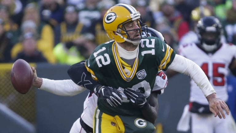 Green Bay's Aaron Rodgers throws the ball as he is hit by the Falcons' De'Vondre Campbell.
