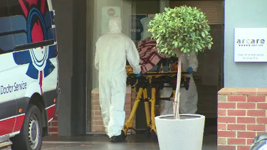 A COVID-positive resident is removed from Arcare's Maidstone home on Sunday.