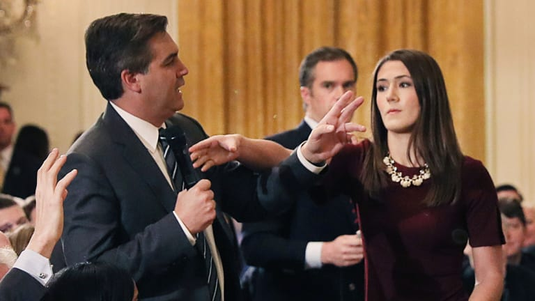 A White House staff member reaches for the microphone held by CNN's Jim Acosta as he questions US President Donald Trump during a news conference.