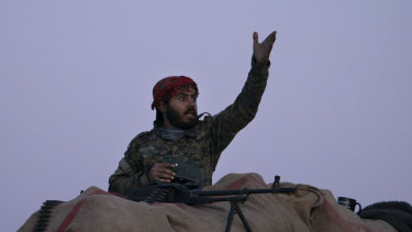 A US-backed Syrian Democratic Forces fighter reacts as an airstrike hits territory still held by Islamic State militants in the desert outside Baghouz, Syria.