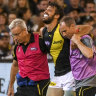 Tigers defender Alex Rance is helped from the field.