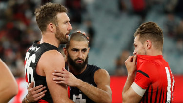 Adam Saad is congratulated by former Bombers team mates Cale Hooker and David Zaharakis.