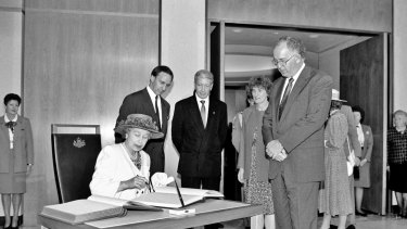 Her Royal Highness Queen Elizabeth II signs the visitors' book at Parliament House, while Prime Minister Paul Keating and Parliament House officials look on, February 1992.
