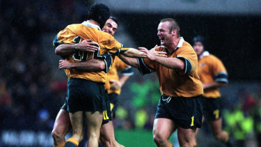 Joe Roff and Richard Harry swamp Stephen Larkham after his field goal in extra time won Australia's semi-final against South Africa in the 1999 World Cup.