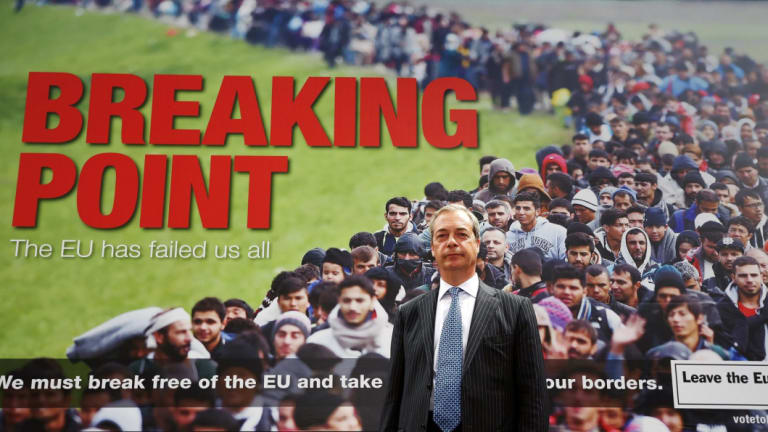 """Leader of the UK Independence Party Nigel Farage with the infamous """"Breaking Point"""" poster during the Brexit campaign."""