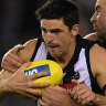 Wrapped up: Pies captain Scott Pendlebury is stopped in his tracks by North's Ben Cunnington.