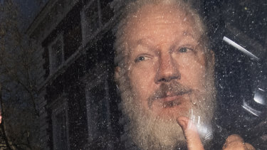 Julian Assange gestures as he arrives at Westminster Magistrates' Court.