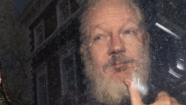 Julian Assange gestures as he arrives at Westminster Magistrates' Court.