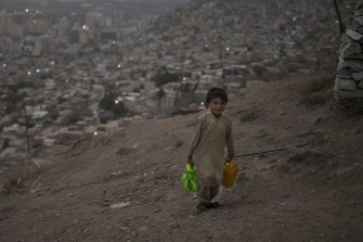 A boy carries water to his home in Kabul, Afghanistan.