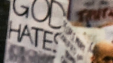 This is a close-up of an altered sign in a photograph from the Women's March in 2017 that is on display at the National Archives in Washington, DC. The original image is populated with a variety of signs. At least four of the signs are altered.