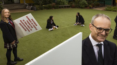 Sydenham CRC Principal Brendan Watson and year 12 students Chloe Jenson, Sirin Mirham, Alicia Azzopardi and Lucas Blackman put up social distancing signs in readiness for their return to school next week.