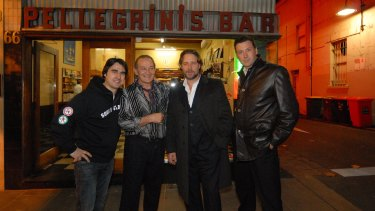 Nick Giannopoulos (left), Sisto Malaspina, Russell Crowe and another man pose for a photo at the front of Pellegrinis Bar in Melbourne.