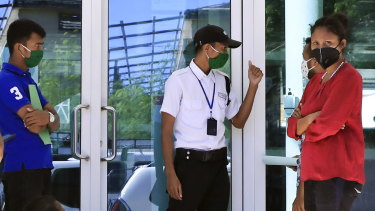 A security guard manages a queue of people waiting to enter a shopping centre in Dili, East Timor.