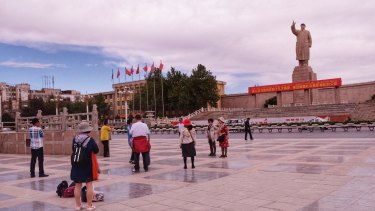 """Han Chinese tourists take photos of a monumental sculpture of Chairman Mao Zedong. A big red sign under the statue encourages people to """"implement the spirit"""" of the communist party and promote """"social stability"""" in Xinjiang."""