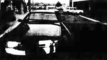 An unmarked cop car bears the scar of a shot fired during the chase. The getaway car is in the background.