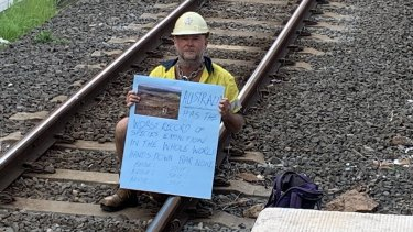 Rick Pass, 54, protests against climate change while chained to railway lines at Bowen Hills on Wednesday morning.