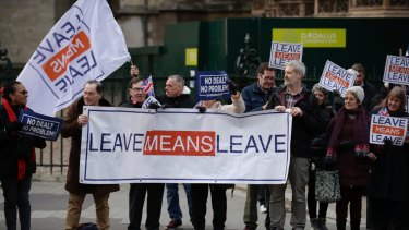 Leave the European Union supporters hold placards and protest across the street from the Houses of Parliament.