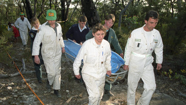 Rescue workers remove the body of a female British backpacker after it was discovered in the Belanglo State Forest on September 20, 1992.