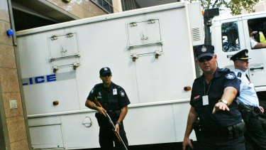 Police guarding the paddy wagon carrying the Pong Su crew members into court