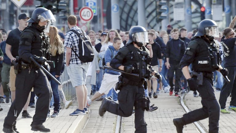 Police officers run during protests in Chemnitz, Germany.