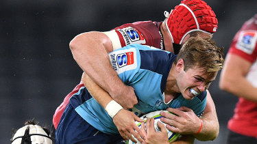 Will Harrison is tackled by Len Massyn at Bankwest Stadium.