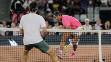 Rafael Nadal advances to the net against Federer.