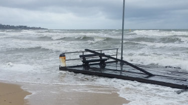 A part of Frankston Pier floats on the shoreline after breaking off during wild weather on Friday.