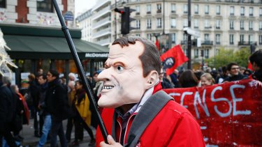 A man wearing a mask of of French President Emmanuel Macron attends a demonstration in Paris this month.