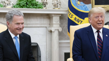 US President Donald Trump speaks while Sauli Niinisto, Finland's president, smiles during a meeting at the Oval Office.