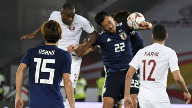 Japan's defender Maya Yoshida (second from right), plays a hand ball in the penalty box.