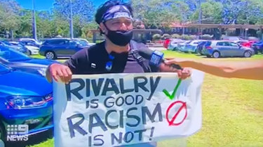 Krishna Kumar holds up his banner in the SCG car park.