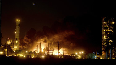 Flames and thick black smoke light up the pre-dawn sky following and explosion at the TPC plant in Port Neches, Texas.