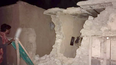 A local resident looks his damaged house in Harnai, Pakistan, on Tursday.