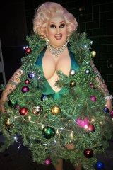Maxi Shield suffers for her art in a Christmas tree dress.