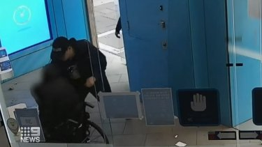 Julian Stewart, in his wheelchair, is robbed by a man at an ANZ branch on George Street, Sydney.