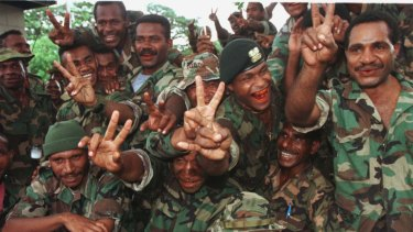 Soldiers of the PNG Defence Forces give the victory sign as they receive news that PM Julius Chan is to step aside.