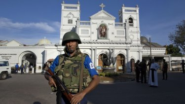 Sri Lankan air force officers and clergy stand outside St Anthony's Shrine a day after the blast in Colombo.