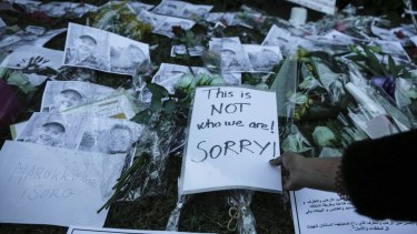 Moroccans lay flowers and messages during a candlelight vigil in Rabat.
